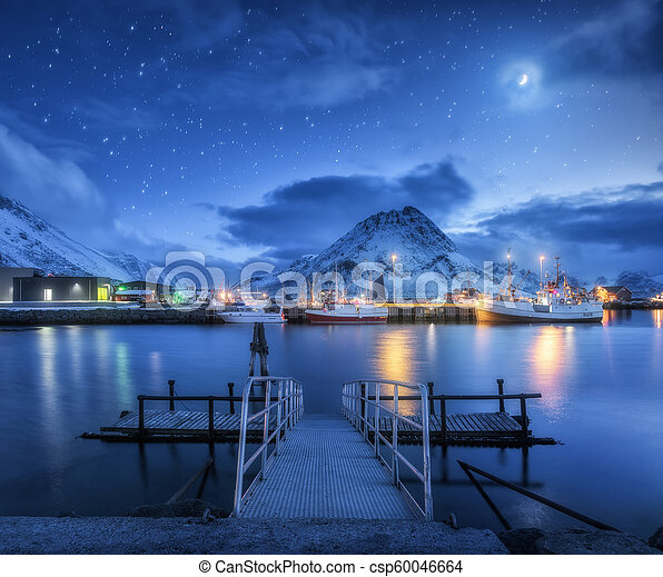 Fishing boats near pier on the sea and snowy mountains at night - csp60046664