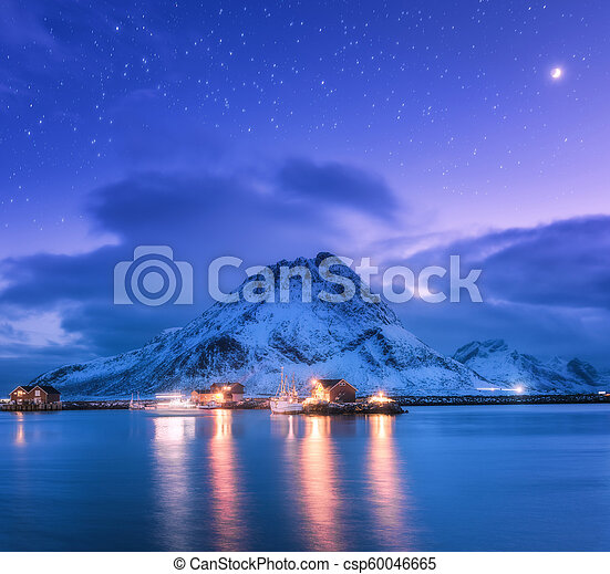 Fishing boats near pier on the sea and snowy mountains at night - csp60046665