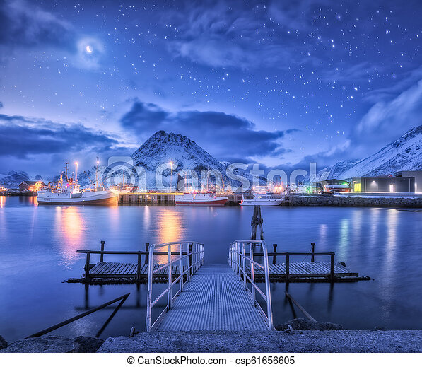 Fishing boats near pier on the sea and snowy mountains at night - csp61656605