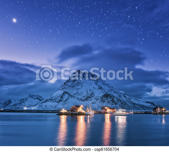 Fishing boats near pier on the sea and snowy mountains at night - csp61656704