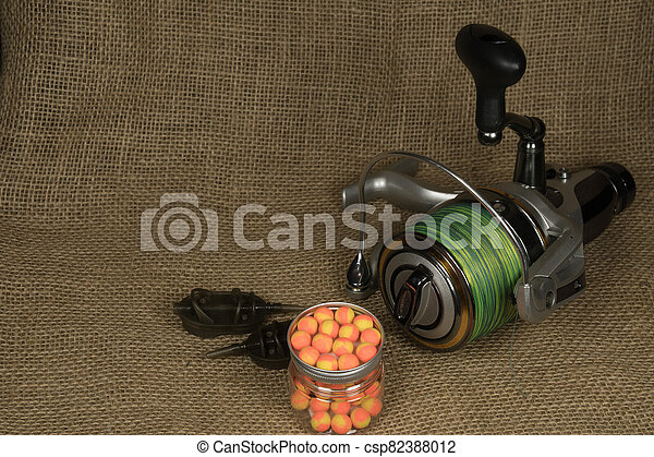 Fishing, carp reel with fishing linel on the background of burlap . Burlap - csp82388012