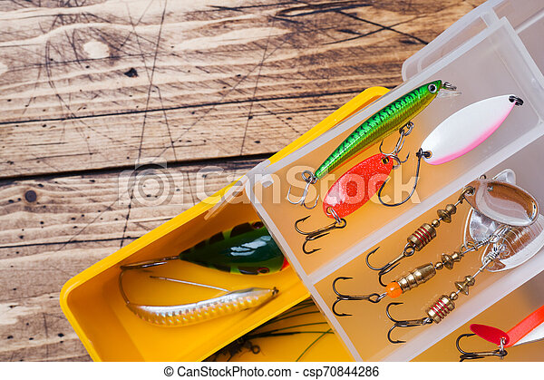 Fishing hooks and baits in a set for catching different fish on a wooden background with copy space. - csp70844286