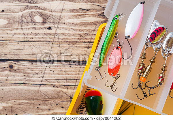 Fishing hooks and baits in a set for catching different fish on a wooden background with copy space. - csp70844262