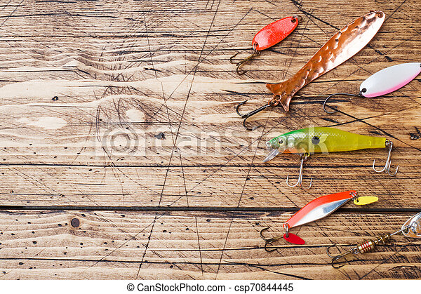 Fishing hooks and baits in a set for catching different fish on a wooden background with copy space. Flat lay - csp70844445
