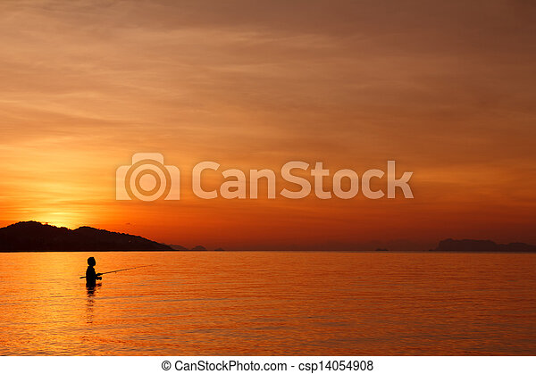 Fishing with spinning on tropical beach at sunset, fisherman silhouette in water - csp14054908