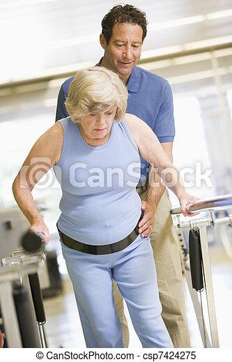 Fisioterapeuta con paciente en rehabilitación - csp7424275