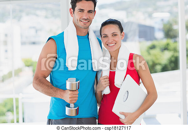 Fit couple with dumbbell and scale in bright exercise room - csp18127117