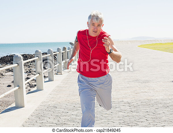 Fit mature man jogging on the pier - csp21849245