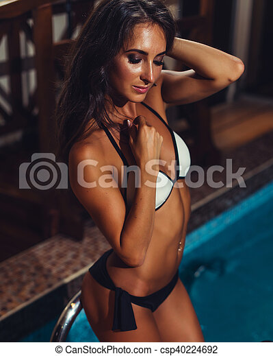 Fit sexy young woman in swimwear standing by a swimming pool - csp40224692