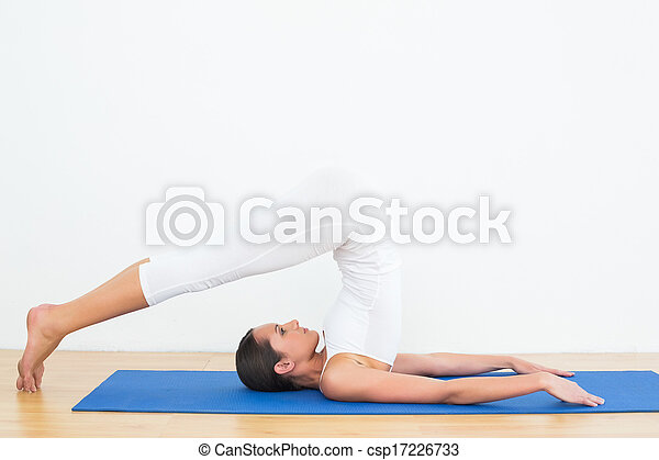 fit woman doing the plough posture in fitness studio full