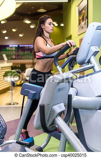 Fit woman exercising at fitness gym aerobics elliptical walker trainer workout. - csp40025015
