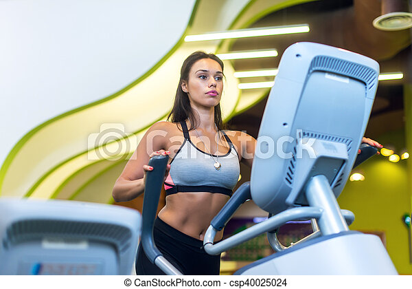 Fit woman exercising at fitness gym aerobics elliptical walker trainer workout. - csp40025024