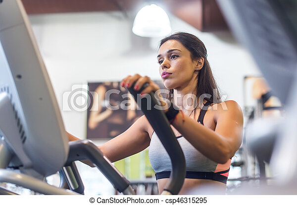 Fit woman exercising at fitness gym aerobics elliptical walker trainer workout. - csp46315295