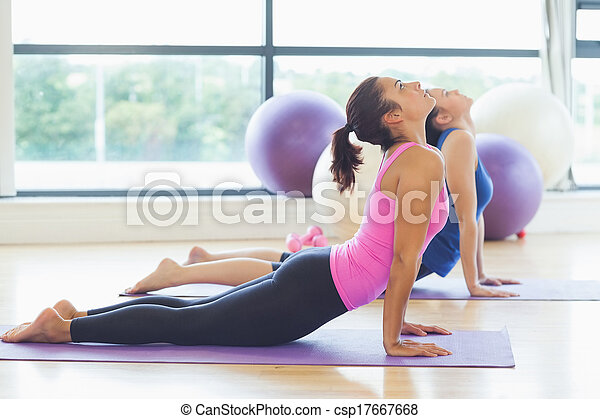 Fit women doing the cobra pose in fitness studio - csp17667668