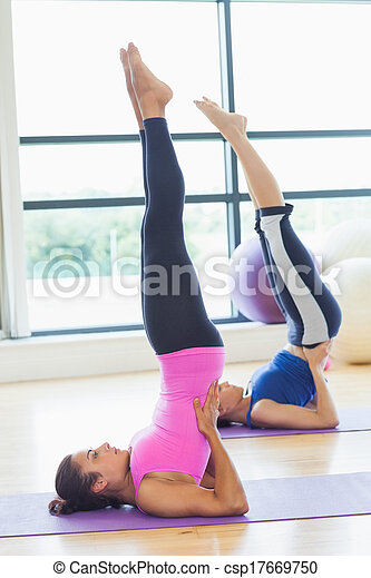 fit women doing the shoulder stand full length side view