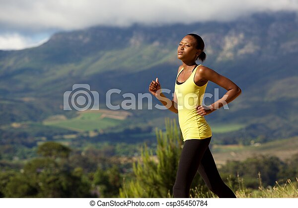 Fit young african woman running outdoors in nature - csp35450784