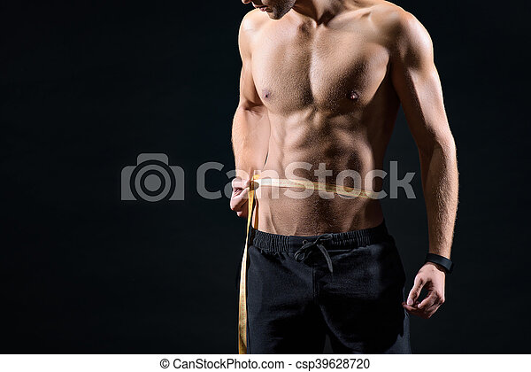 Fit young man taking measurements of body