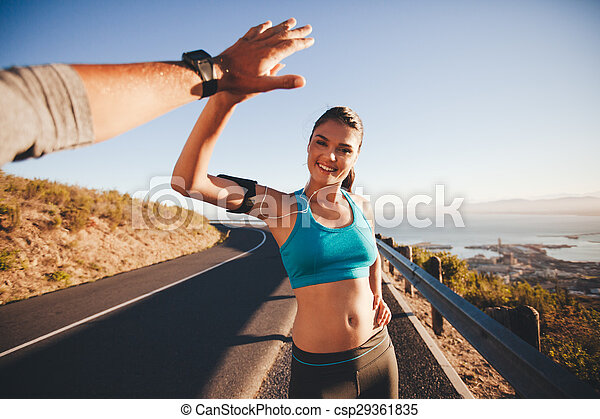 Fit young woman high fiving her boyfriend after a run - csp29361835
