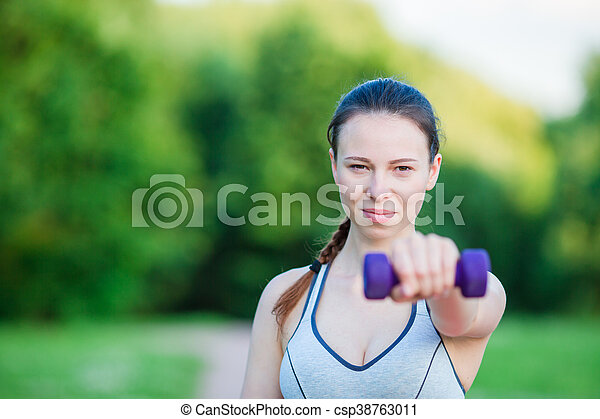 Fit young woman working out with weights outdoors. Active girl working out with small dumbbells in the park - csp38763011