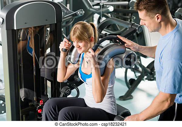 Fitness center young woman exercise with trainer - csp18232421