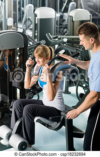 Fitness center young woman exercise with trainer - csp18232694