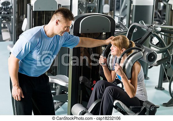 Fitness center young woman exercise with trainer - csp18232106