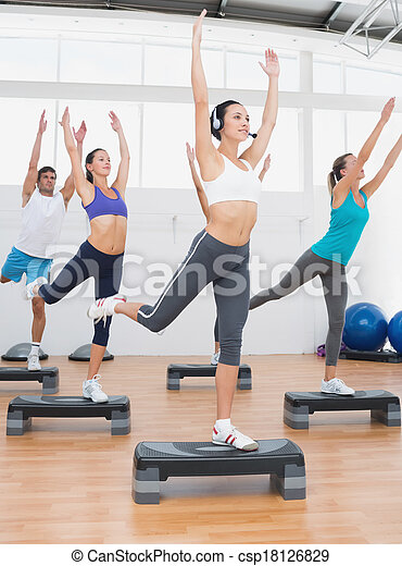 Fitness class performing step aerobics exercise - csp18126829
