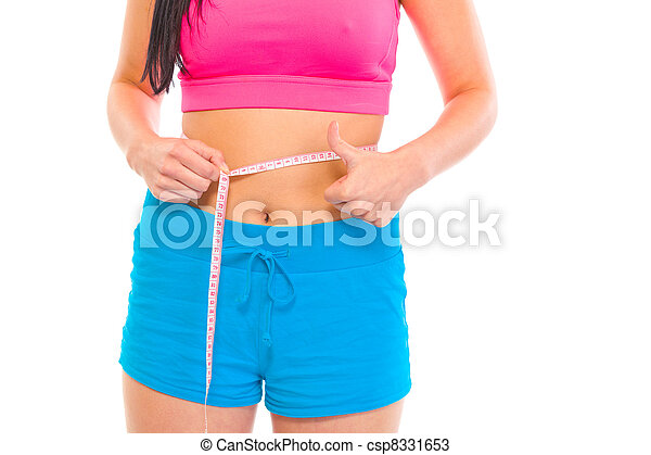 Fitness girl measuring her waist and showing thumbs up gesture isolated on white. Close-up.