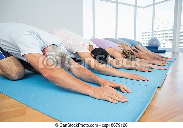 Fitness group in row at yoga class - csp18679126
