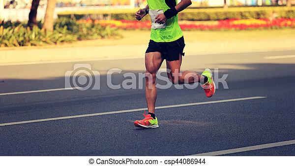 fitness male marathon runner running on city road - csp44086944