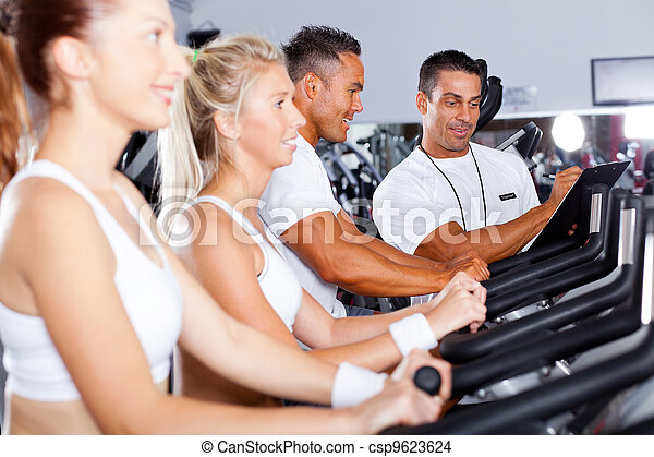 fitness people biking in gym with personal  - csp9623624