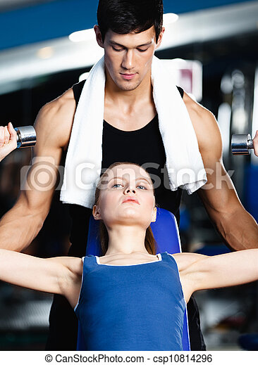 Fitness trainer helps woman to exercise with weights - csp10814296