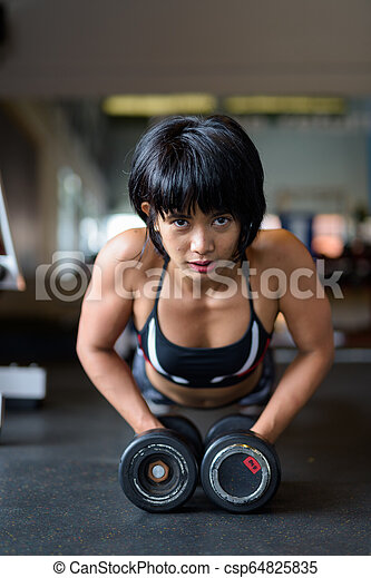 Fitness Woman Doing Plank With Dumbbells In Gym