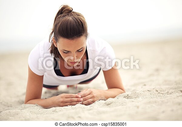 Fitness Woman on the Beach Doing Core Exercises - csp15835001