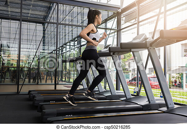 fitness woman running on running machine at gym fat