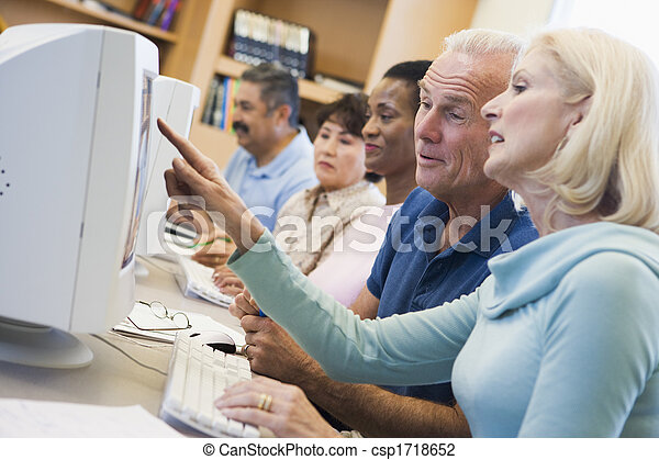 Five people at computer terminals in library (depth of field) - csp1718652