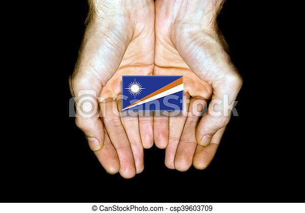 Flag of Marshall Islands in hands on black background - csp39603709