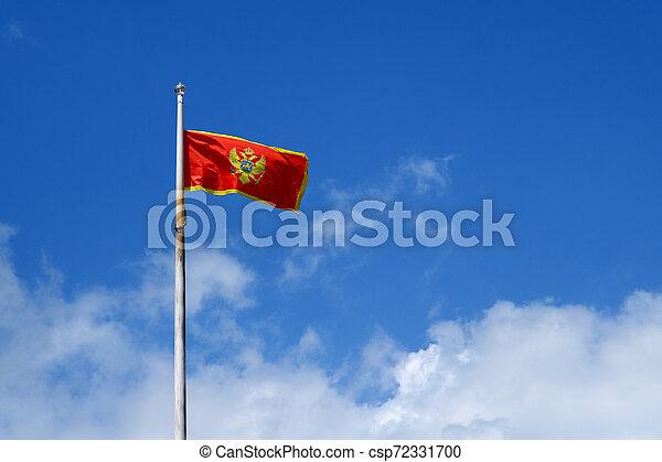 Flag of Montenegro on blue sky background - csp72331700