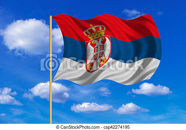 Flag of Serbia waving on blue sky background - csp42274195