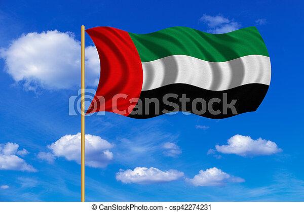 Flag of the UAE waving on blue sky background - csp42274231