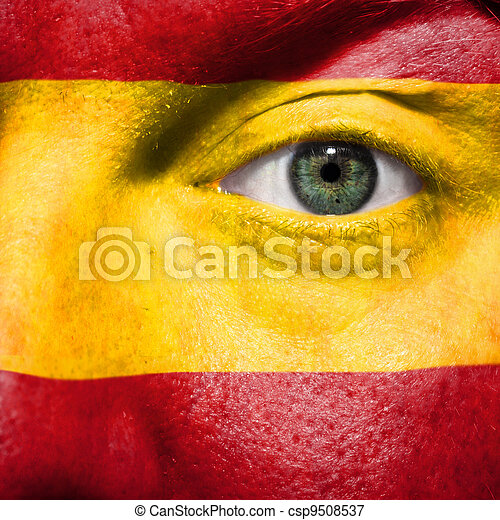 Flag painted on face with green eye to show Spain support in sport matches - csp9508537