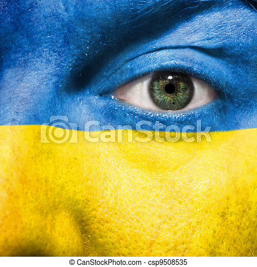 Flag painted on face with green eye to show Ukraine support in sport matches - csp9508535