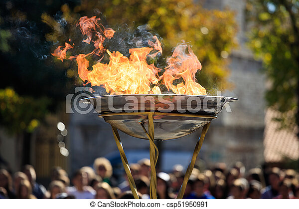 Flame lighting ceremony. Flame in front of blurred crowd - csp51950991