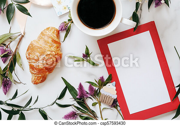 Flat lay desk with flowers, pretzel, cup of coffee - csp57593430