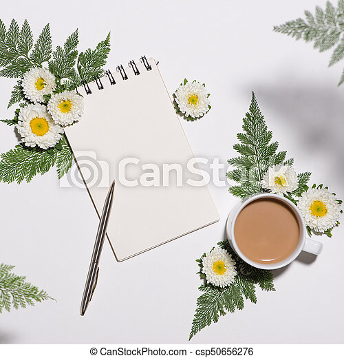 Flat lay of green leaves and flowers pattern with cup of coffee and paper note on white background - csp50656276