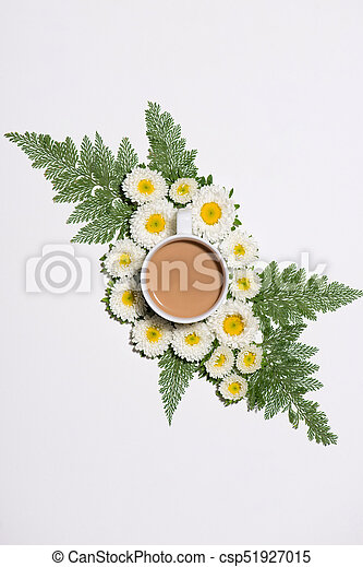 Flat lay of green leaves and flowers pattern with cup of coffee on white background - csp51927015
