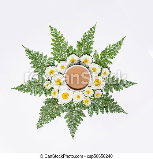 Flat lay of green leaves and flowers pattern with cup of coffee on white background - csp50656240