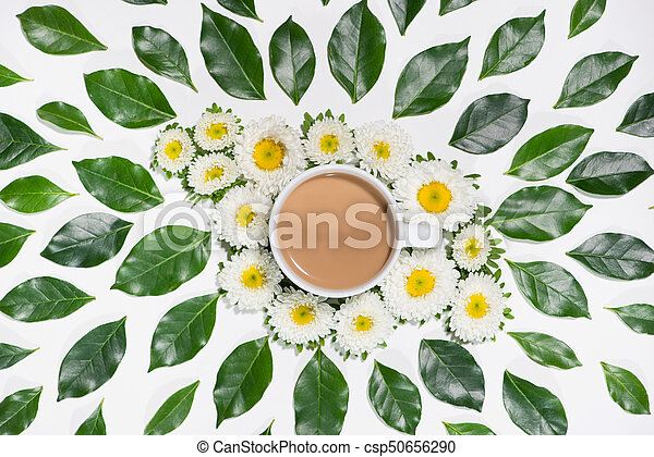 Flat lay of green leaves and flowers pattern with cup of coffee on white background - csp50656290