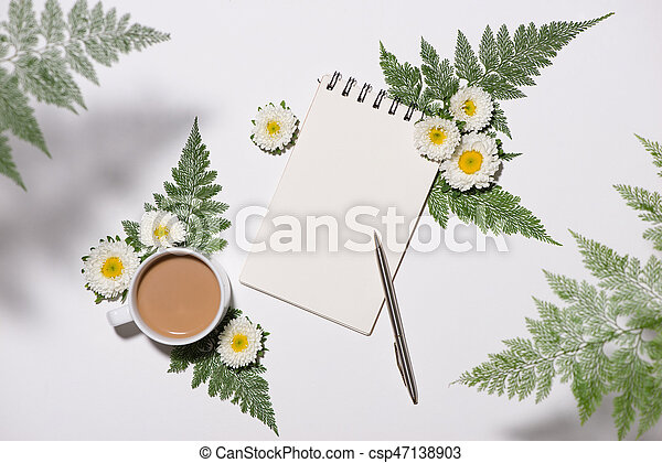 Flat lay of green leaves and flowers pattern with cup of coffee and paper note on white background - csp47138903