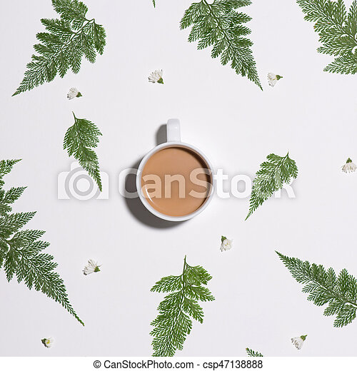 Flat lay of green leaves pattern with cup of coffee on white background - csp47138888